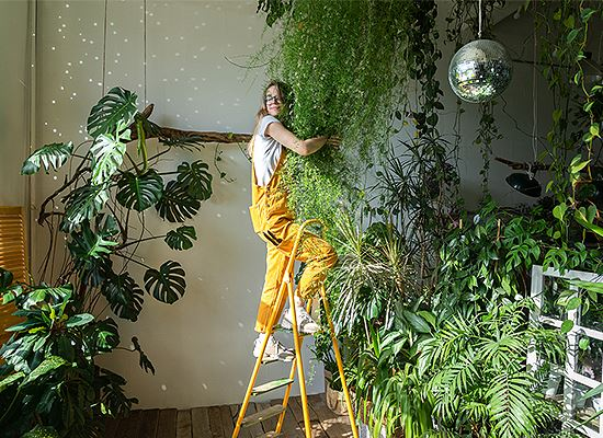 Tropical plants indoors woman hugging them